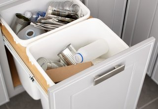 Trash cans tucked inside of a kitchen cabinet door or drawer.